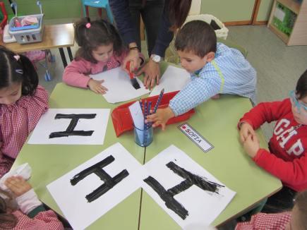 Los niños dibujando la H de logo.