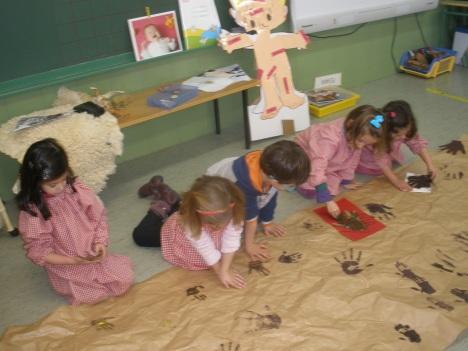 niños estampando manos para la decoración de la cueva